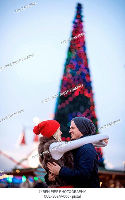 Romantic young couple hugging at xmas festival in Hyde Park, London, UK