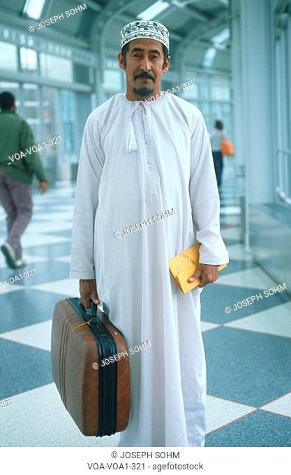 Middle Eastern man wearing white robes holding suitcase, JFK Airport, New York
