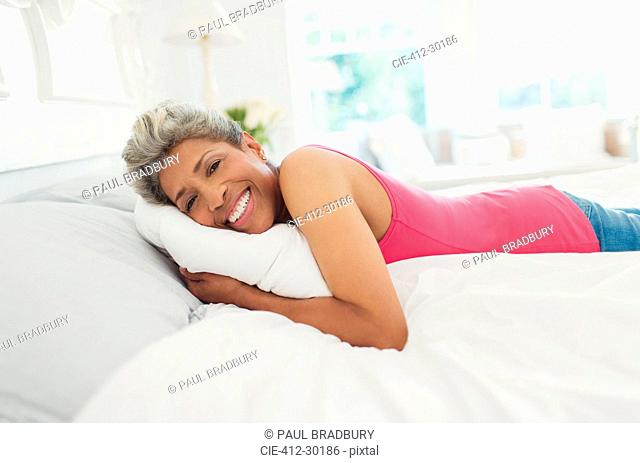 Portrait smiling mature woman laying on bed