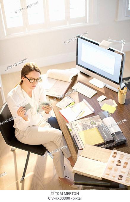 Interior designer examining swatches at desk in home office
