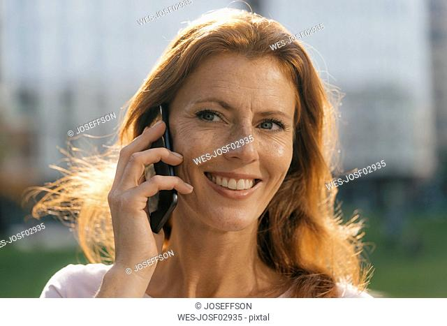 Portrait of smiling businesswoman on cell phone outdoors in the city