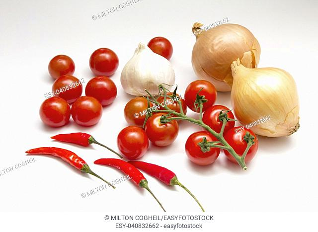 An arrangement of onons, tomatoes, chillies and garlic on a white background