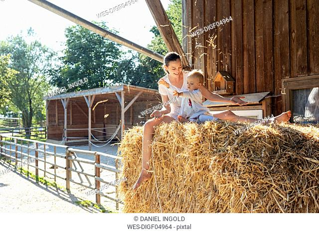 Happy mother and little daughter playing with straw in a barn