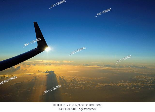 Wing tip of Boeing 737-800 airliner plane at sunset over Atlantic Ocean