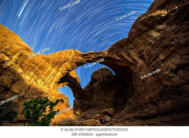 Circumpolar star trails spinning behind Double Arch at Arches National Park, Utah, as the waning gibbous Moon lights the arches toward the end of the sequence