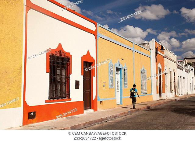 Young man walking in front of colorful colonial buildings at the city center, Merida, Yucatan Province, Mexico, Central America