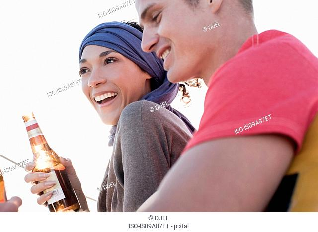 Couple on yacht, woman holding beer bottle