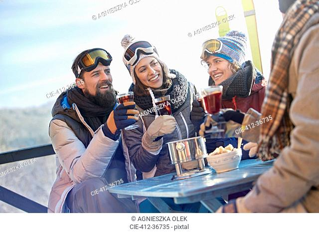 Skier friends drinking and eating at balcony table apres-ski