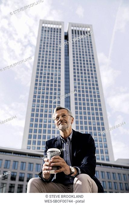 Grey-haired businessman in front of skyscraper holding coffee to go