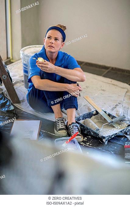 Woman decorating, taking a break, sitting on floor holding apple