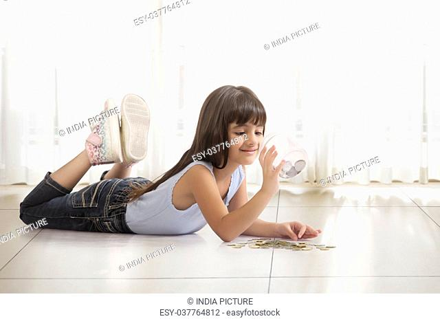 Little girl lying on floor looking in money box