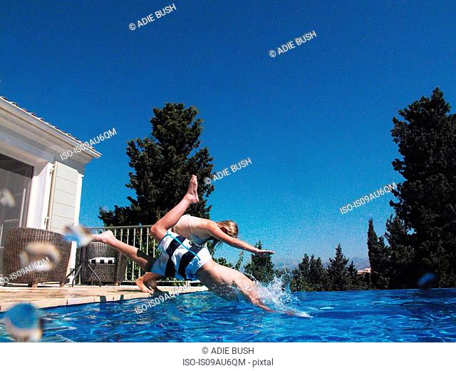 Girl and teenage brother diving into apartment swimming pool