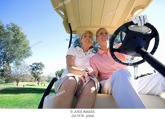 Mature couple sitting in golf buggy on golf course, man driving, smiling, front view, low angle view