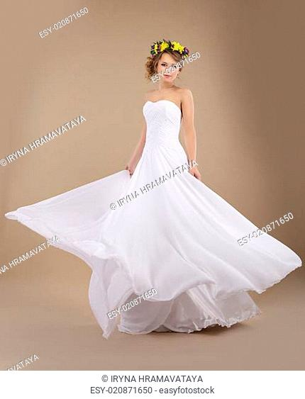 Beautiful Fiancee with Vernal Wreath of Flowers in Flying Wedding Dress