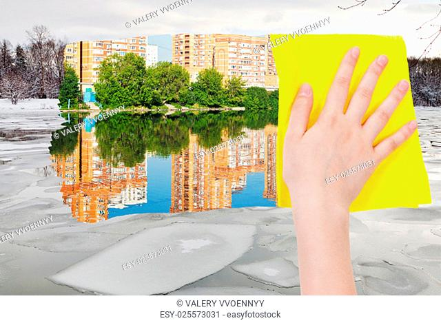 season concept - hand deletes ice block in winter river by yellow cloth from image and summer cityscape is appearing