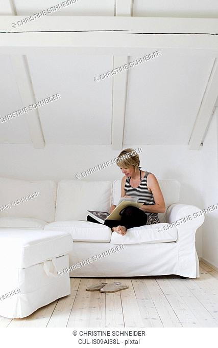Mature woman sitting cross legged on sofa reading book