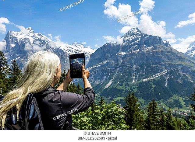 Caucasian woman photographing mountain with digital tablet