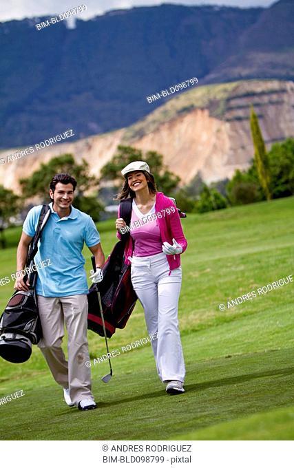 Hispanic couple playing golf together