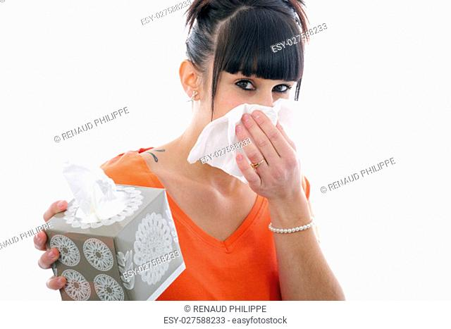 sick young brunette girl blowing her nose isolated on white background