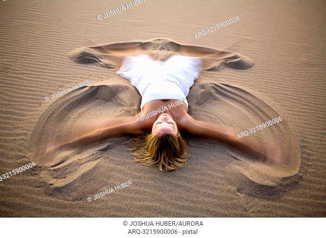 A woman in white making a sand angel on the Stovepipe Wells Dunes in Death Valley, California