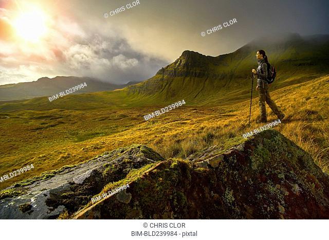 Caucasian woman hiking in green mountain landscape