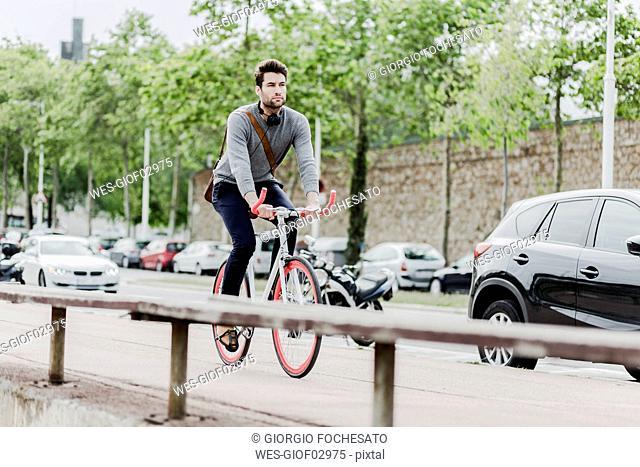 Young man riding racing cycle