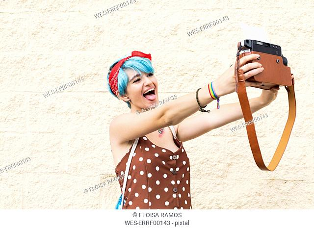 Portrait of young woman with blue dyed hair taking selfie with instant camera