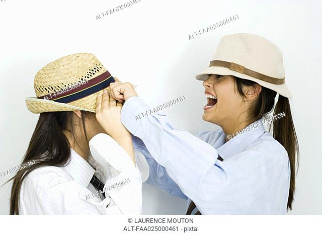 Teenage girl pulling hat over her friend's face, laughing