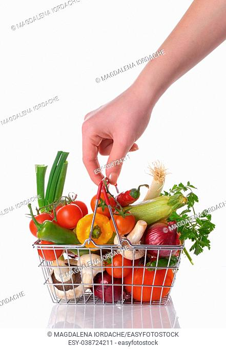 Raw vegetables and hand in basket isolated on white