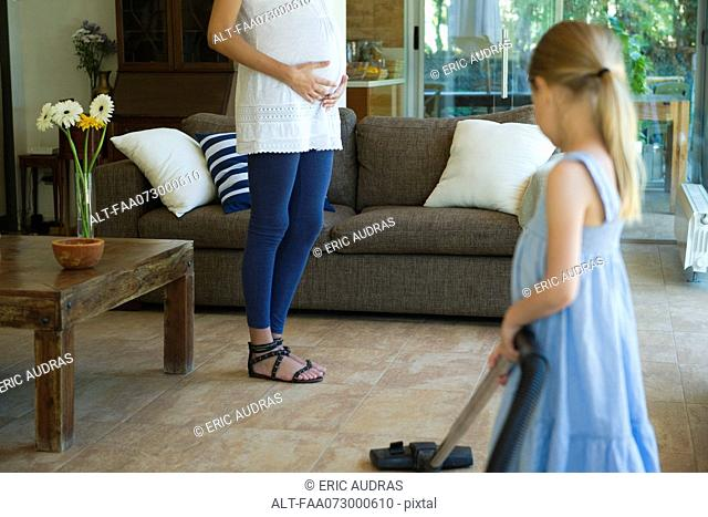 Daughter helping pregnant mother vacuum floor, cropped