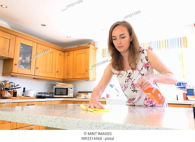Caucasian woman cleaning kitchen counter
