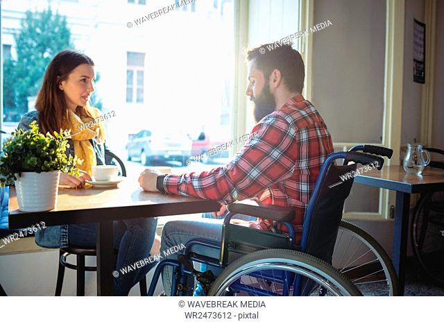 Disabled hipster with woman at cafe