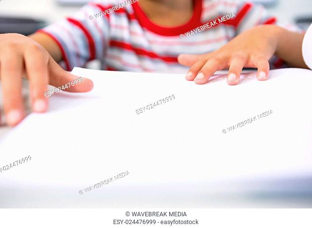 Child touching braille book in classroom