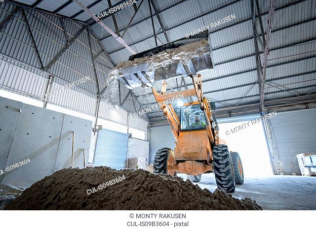 Digger with sand in architectural stone factory
