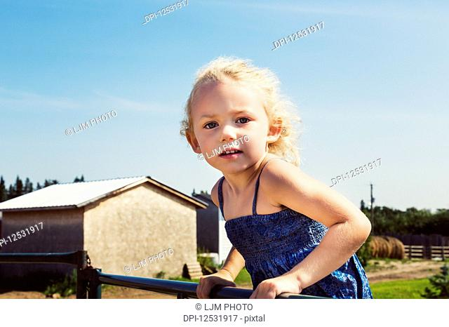 Close-up of a little girl with blond, curly hair standing on a metal fence on a farm and looking at the camera; Edmonton, Alberta, Canada