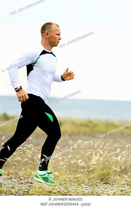Young man running at coast