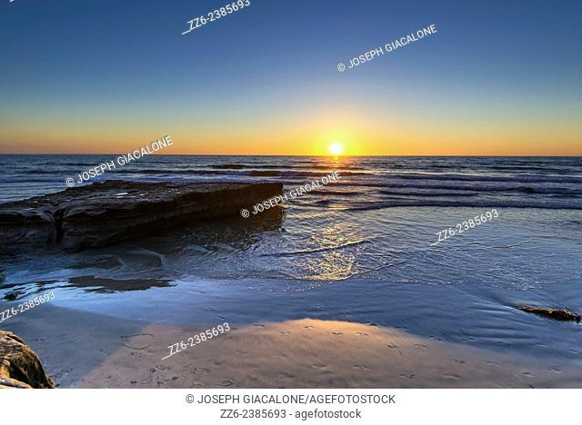 The Sun setting with a view of Flat Rock on Torrey Pines State Beach. San Diego, California, United States