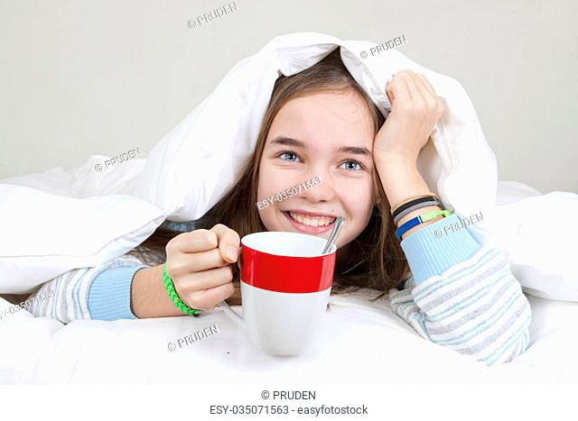 Happy girl eating breakfast in bed with a cup of cafè