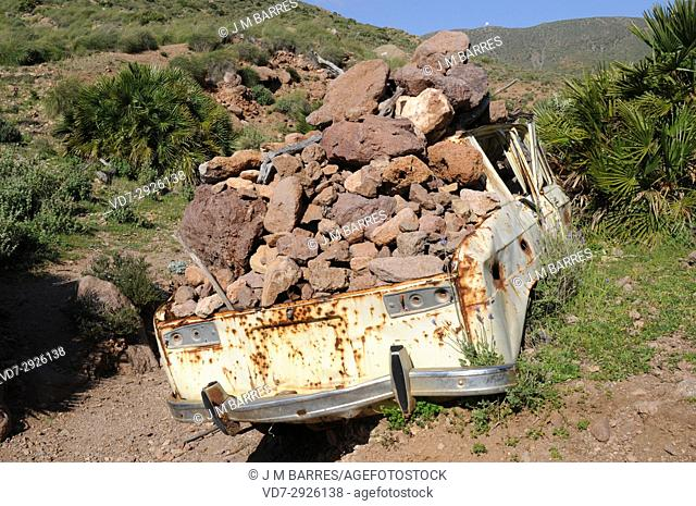 Caldera de Majada Redonda; abandoned car loaded with stones. Cabo de Gata-Nijar Natural Park, Almeria province, Andalucia, Spain