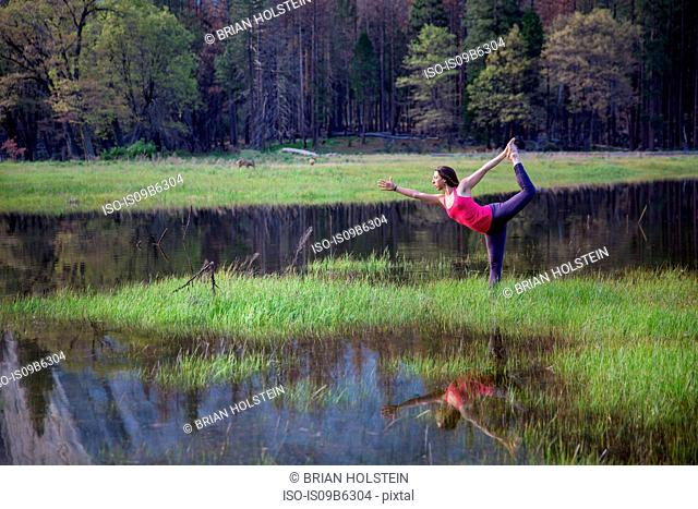 Woman practicing yoga tree pose by lake in Yosemite National Park, California, USA