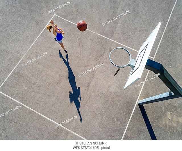 Aerial view of young woman playing basketball