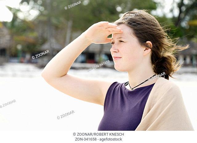 Junge Frau am Strand hält die Hand über die Augen, um weiter schauen zu können Model: Marlene