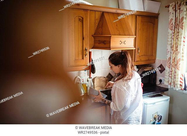Woman standing and preparing meal in kitchen