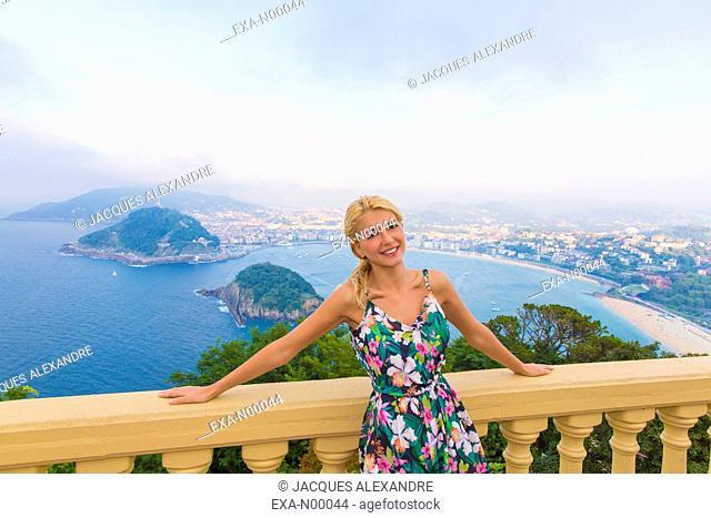 Woman leaned at a balcony looks at La Concha Bay, San-Sebastian, Gipuzkoa, Spain