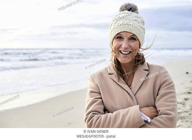 Spain, Menorca, portrait of happy senior woman on the beach in winter