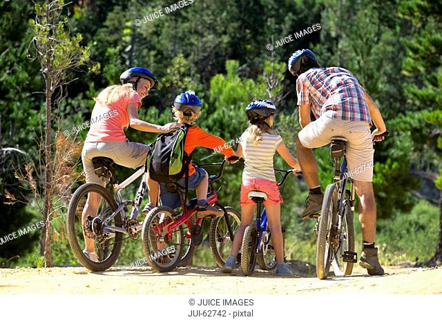 Family riding mountain bikes in forest