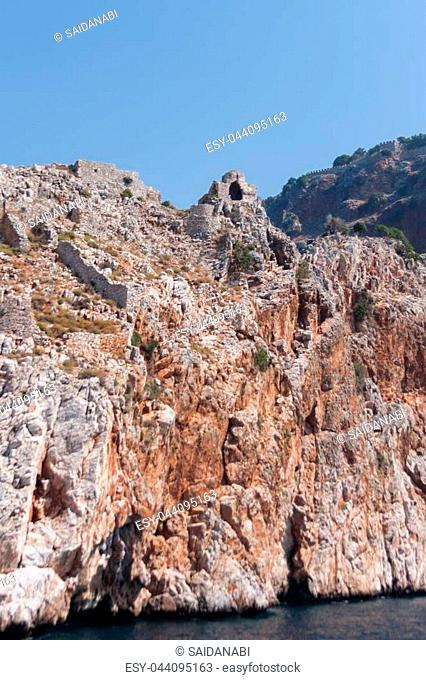 View from sea of ancient walls and remains fo ancient monastery located on cape Jilvarda in Alanya castle rock shot on sunny day
