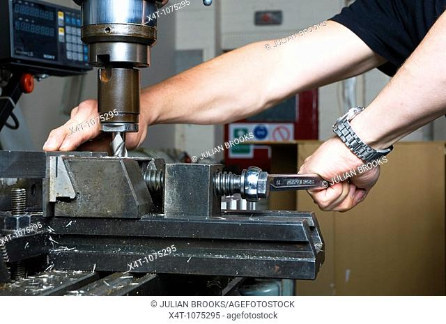 clamping a part in place in a milling machine using a machine vice, tightening with a spanner, precision engineering