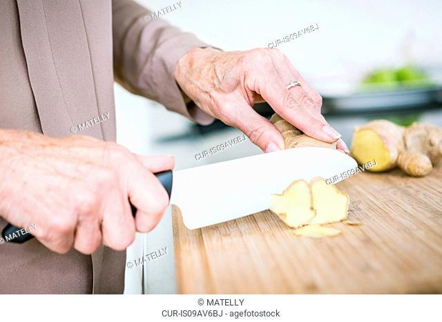Close up of senior female hands chopping ginger