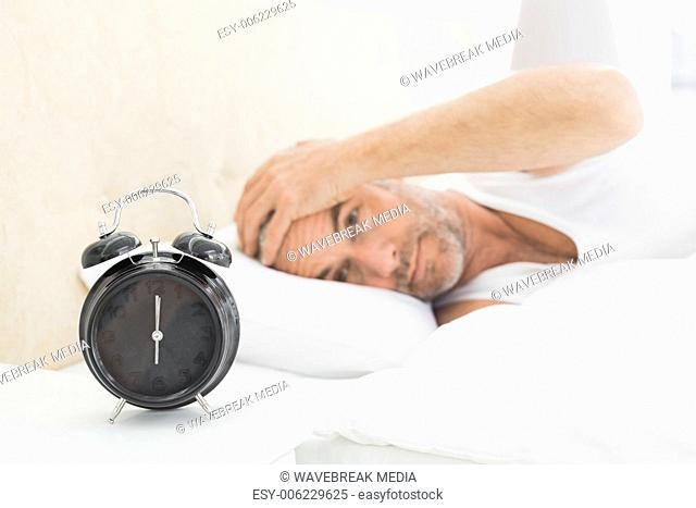 Man resting in bed with alarm clock in foreground